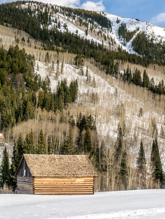 log cabin in snow: Log cabin at base of mountain on a sunny day in winter Editorial