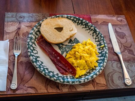 place setting: Breakfast place setting; eggs, bagel, bacon Stock Photo