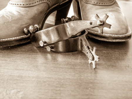 Boots and spurs; wood foreground Stock Photo