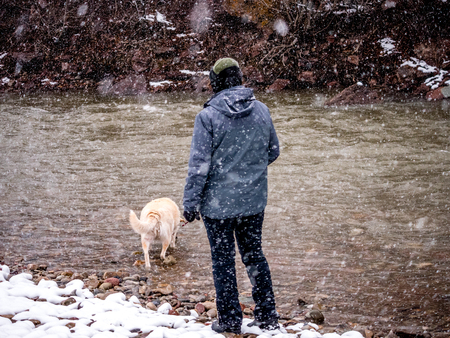 yellow yellow lab: Woman and her Labrador  at a river in snow storm Stock Photo