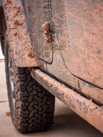 Close up of off-road vehicle covered in red mud Stock Photo