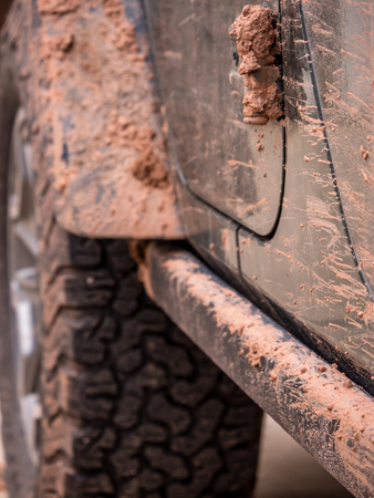 Close up of red mud spattered, caked off road vehicle
