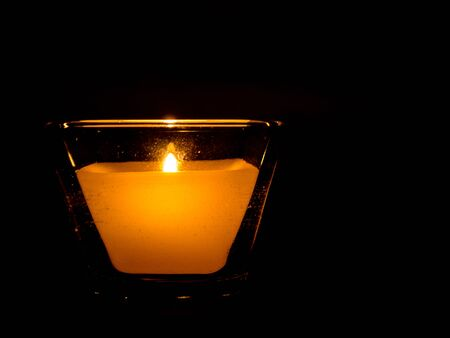 lit candle: Lit candle in square glass surrounded by darkness Stock Photo