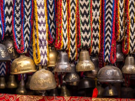Yak bells hung from colorful knit ribbons, close up
