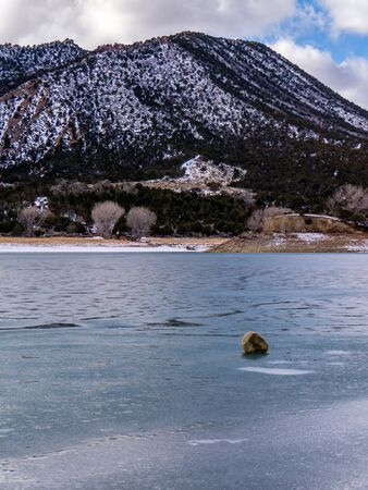 orientation: Isolated boulder on frozen lake surface, portrait orientation