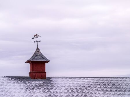 Metal weather vane with horses over snowy, shingles roof Stock Photo