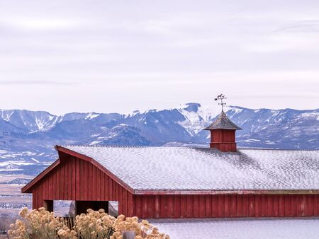 Red sided barn with weather vane in front of snowy mountains