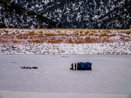 group of ice fishermen on frozen lake next to shelter