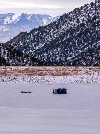 Group of ice fishermen on frozen lake with dog, portrait orientation