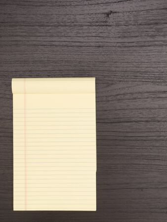 yellow notepad: Wood Desk With Yellow Notepad Stock Photo