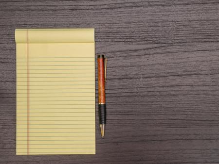 pad and pen: Dark Wood Desk, Yellow Pad, Pen on Desk