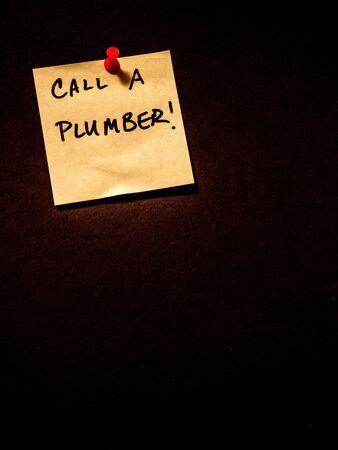 Call a plumber, post it note on black, portrait orientation Stock Photo