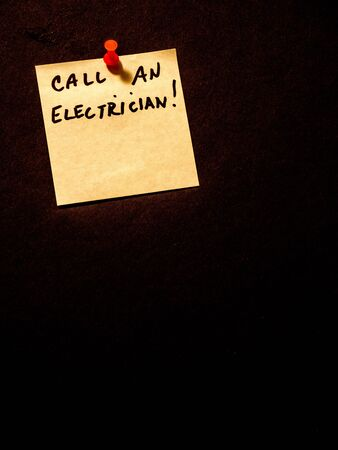 Call an electrician, post it note on black, landscape orientation