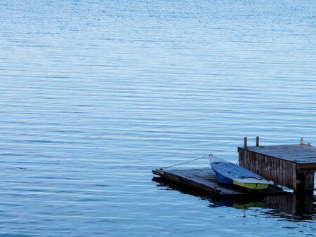 small boat, wooden dock, landscape orientation.