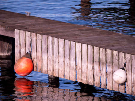 Wood dock with round floats, reflections and copy space Stock Photo