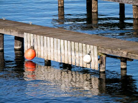 wood dock with round floats, reflections and copy space