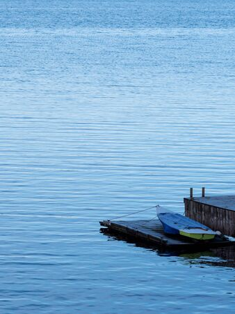 small boat, wooden dock, portrait orientation.