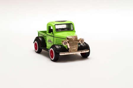 Lichtgroene retro uitstekende auto, stuk speelgoed model dat op witte achtergrond wordt geïsoleerd. Retro auto