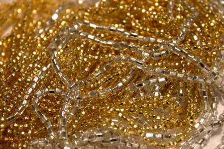 seed beads: This is a closeup photograph of Gold and silver Glass seed beads background