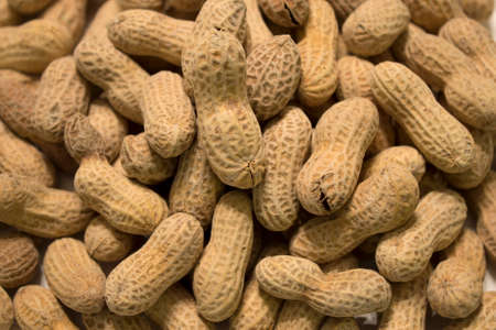 This is a photograph of salted and roasted peanuts in the shell