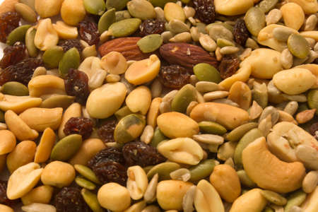 This is a photograph of seeds,peanuts,raisins and almonds Banco de Imagens
