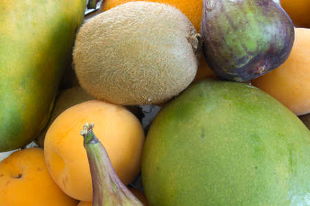 This is a photograph of Mango,Apricot,Orange,Figs and Kiwi