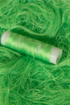 This is a photograph of Neon Green sewing thread roll background 写真素材