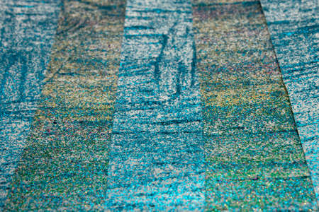 This is a photograph of an abstract background created by organizing stripes created using Blue,turquoise,green,pink and gold glitter paint
