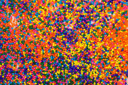 This is a background of colorful neon colored round sprinkles background