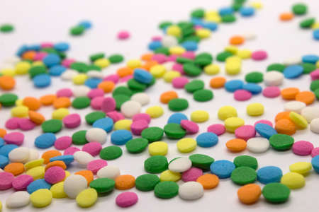 This is a photograph of colorful round sprinkles isolated on a White Background