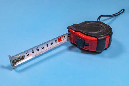 Tape-line is the most popular measuring device isolated on a blue background