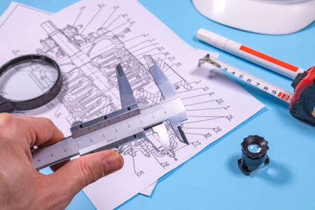 Ndt inspector or an expert is analysing pump blueprints before performing control operations.  Stock Photo