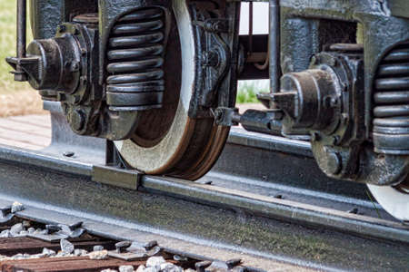 Old rusty railroad wagon weels with a chock brake. Stock Photo