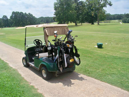 golf cart with bags near driving range