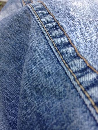 denim: The seam of a light blue denim jeans.