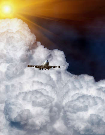 airplane flying into the clouds in a summer day
