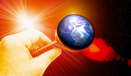 Earth under hand with  magnifying glass and powerful star  Stock Photo
