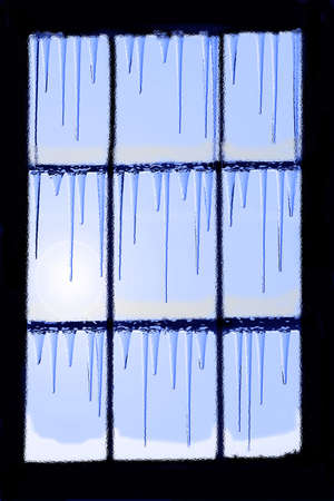 window in the cold season with icicles and sun light