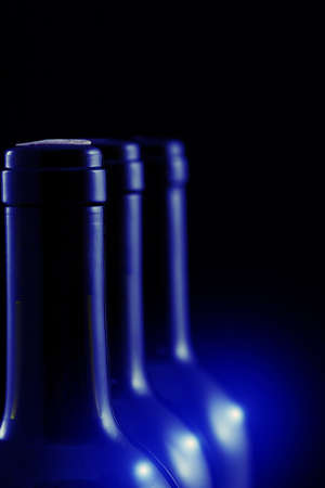 wine bottles in row with blue light reflections