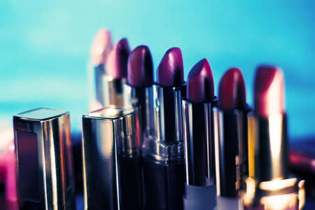 row of lipsticks on blue white background