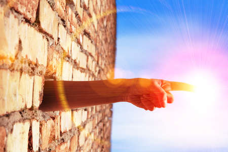 hole in wall: hand breaking wall to touch the sun