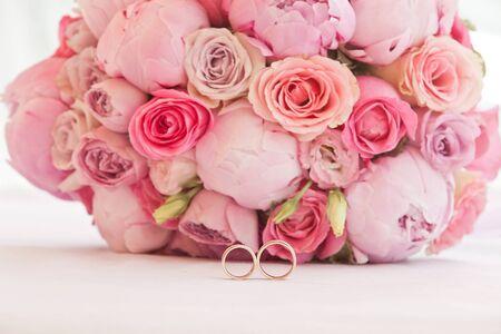 Hermoso ramo de peonías y otras flores rosas con anillos de boda para recién casados.
