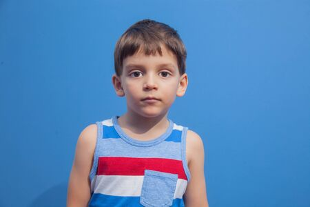a young boy in a striped t-shirt poses as a model on a blue background Stockfoto
