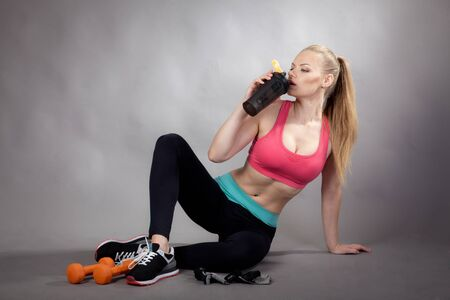 young athletic woman works out with dumbbells to improve her figure