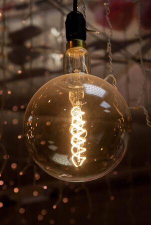 Luminous thread of a retro Edison lamp on a dark background