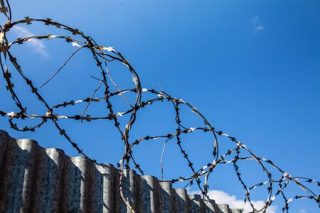 barbed wire over a high fence protects against illegal entry into the territory