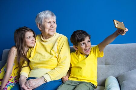 An old grandmother and her beloved grandchildren sit at home and take photos on their smartphone