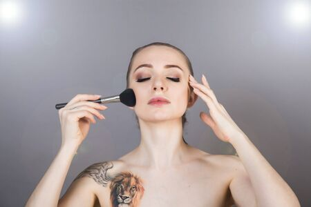 beautiful girl with healthy skin relaxes after a Spa and applies makeup with a brush Banque d'images