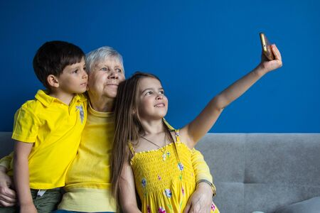 An old grandmother and her beloved grandchildren sit at home and take photos on their smartphone 写真素材