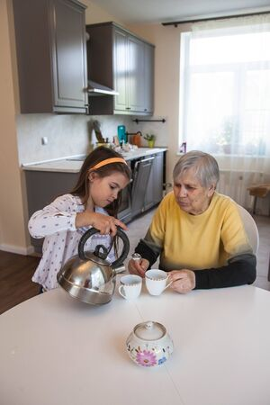 Grandmother and granddaughter drink tea sitting at the white table in the kitchen